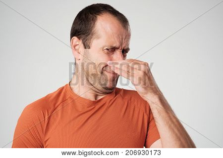 Caucasian man is pinching nose with fingers and looking with disgust because of bad smell isolated on white background. Negative human face expression body language reaction
