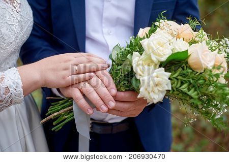 bride put her hand on the bridegroom's hand with the wedding bouquet