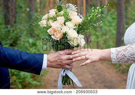 bridegroom gives the bride a wedding bouquet for a walk in the park.