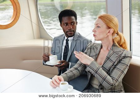 Confident co-workers having coffee at break during business trip on steamer