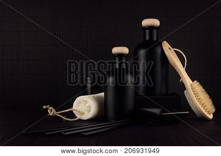 Cosmetics mock up - blank black bottles bath accessories on dark wood board copy space. Template for advertising designers branding identity cover.
