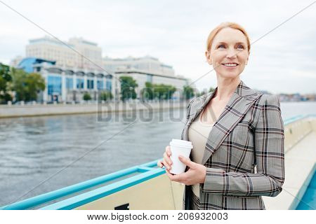 Happy woman with drink standing by riverside during travel on steamer