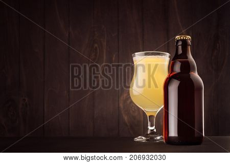Brown beer bottle belgian steinie and glass tulip with muddy weizen on dark wood board copy space mock up. Template for advertising design branding identity.