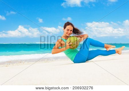Young woman abdominal exercise on sea beach to keep fit and health. Doing crunches core leg raising and twisting exercises with coconut weight. Girl doing abs workout. Summer family sports holidays.