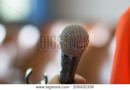 blurred of hands holding businesspeople speech and speaking with microphones in seminar talking conference hall light with microphones and keynote.