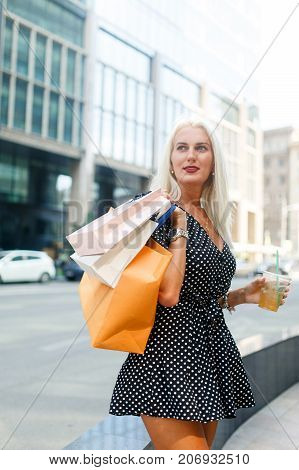 Photo of woman with purchases in bags near city buildings during day