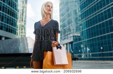 Photo of young woman in dress with purchases on city street near modern buildings