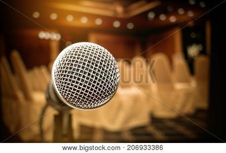 Microphone on abstract blurred of front podium and speech in seminar room or speaking conference hall light Event meeting bokeh background black and white tone