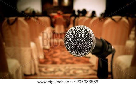 Blurred of microphones in seminar room talking speech in conference hall light with microphone and keynote. Speech is vocalized form of communication humans vintage tone.