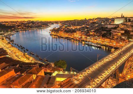 Aerial view of Dom Luis I on Douro River at twilight from Miradouro da Serra do Pilar at Vila Nova de Gaia, Porto, Portugal. The iron arch bridge is icon and symbol of city. Scenic urban skyline.