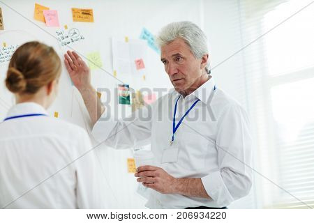 Confident mature private investigator and his young assistant gathered together at investigation board and making assumptions about possible motives of crime