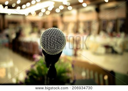 Microphone on abstract blurred of front podium and speech in seminar room or speaking conference hall light Event meeting bokeh background.