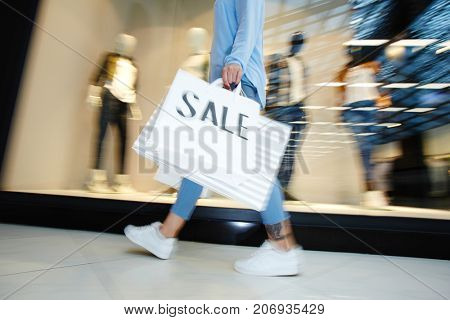 Modern customer carrying paperbags while going along window display of clothing department
