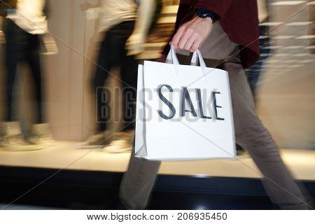 Hurrying guy with shopping bag moving slong window display in the mall during seasonal sale