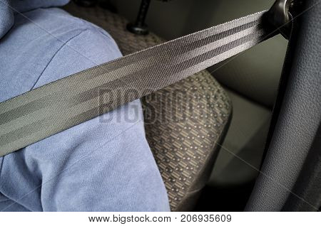 Driver man is fastened with a safety belt while driving the car