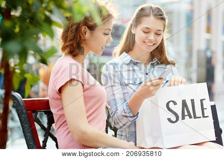Two happy shoppers ordering something to eat after hard shopping in the mall