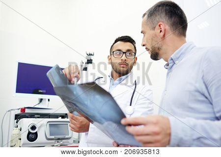 Highly professional radiologist analyzing X-ray images of middle-aged patient and giving necessary recommendations, interior of modern office on background