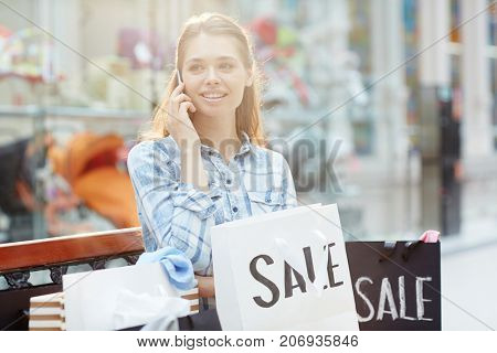 Modern mobile shopper with paperbags speaking on smartphone after shopping