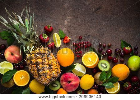 Fruit and berries on dark stone table. Top view with copy space. Pineapple citrus fruit and berry mix.