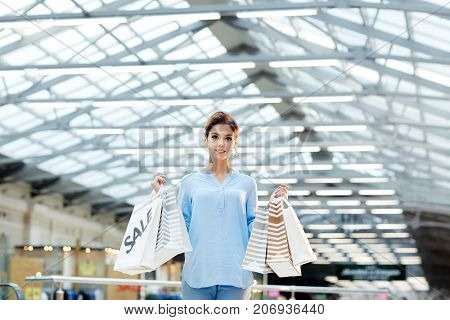 Happy girl in casualwear holding paperbags with gifts bought on sale