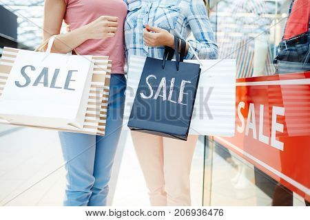 Young friendly women in casualwear holding shopping-bags after black friday sale