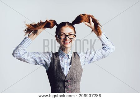 girl-teacher with glasses laughs, keeps herself for pigtails on a white background