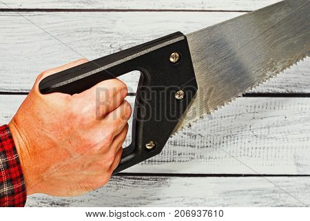 Hand Holding A Hand Saw