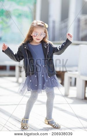 Little cute girl 5 years old, blond long hair, cute smile, big light pink glasses in the form of drops, dressed in a black leather jacket with a shiny snake and blue sleeveless dress posing outdoors alone on a sunny spring day