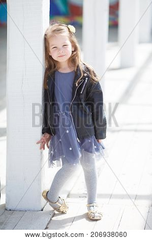 Little cute girl 5 years old, blond long hair, cute smile dressed in black leather jacket with shiny snake and blue sleeveless dress posing outdoors alone on a sunny spring day