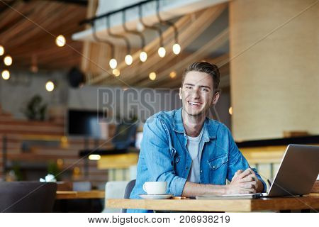 Cheerful blogger sitting in cafe and browsing in the net at leisure
