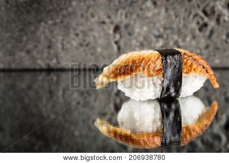 Nigiri sushi with eel over concrete background