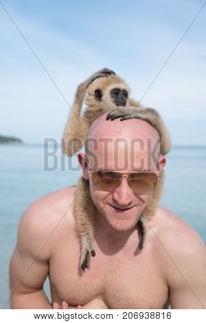 Portrait of smiling man in sunglasses with gibbon monkey on the beach over blue sea and sky background