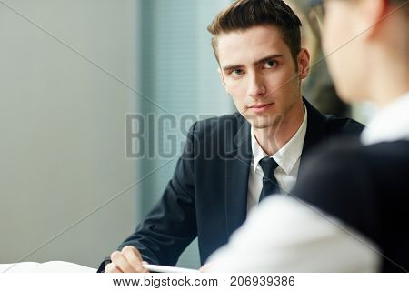Serious employer listening attentively to young candidate for vacancy