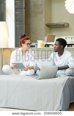 Multi-ethnic young couple calculating their bills while sitting on cozy bed in lotus position, interior of modern studio apartment on background