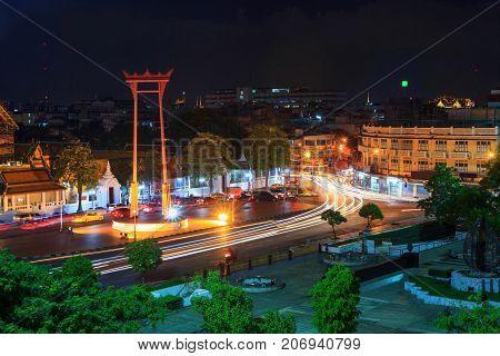 Giant Swing Landmark In Bangkok City In Night Time With Blur Light Of Car Traffic