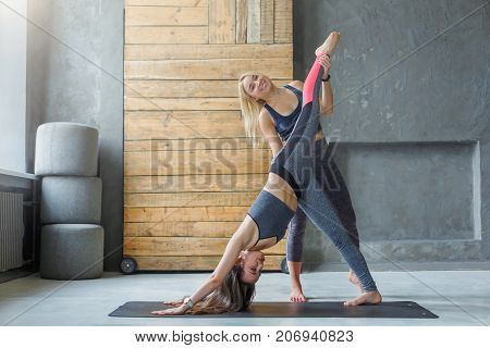 Yoga teacher and beginner in class, making asana exercises. Young woman making one-legged downward-facing dog pose. Healthy lifestyle in fitness club. Stretching with coach