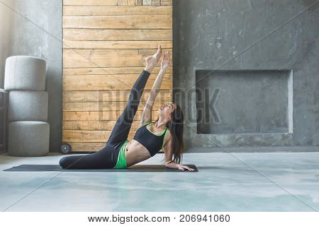 Young woman doing yoga asana. Fit girl stretching at sport club. Healthy lifestyle in fitness club, copy space on wall