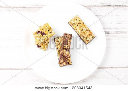 Chocolate, fruits and berries granola bars closeup on white background