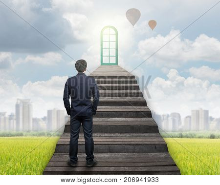 Businessman standing for walking up stairs to the door over the grass and cityscape backgroundSuccess business and Ambitions concept, 3D illustration