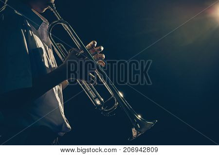 Young student Musician playing the Trumpet with spot light and len flare over dark background on the stage Musical concept