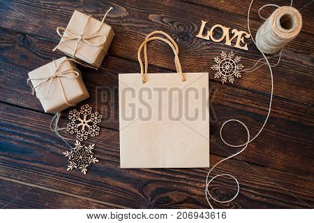 Mockup Paper bag from kraft paper and Christmas gift boxes on a wooden background.