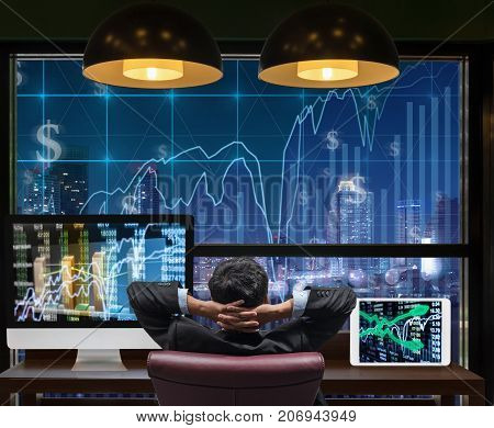 Back side of sitting businessman who is looking at stock market exchange graph over the cityscape on the big screen background and desktop computer with tablet showing the trading graph trade concept, 3D illustration