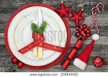 Christmas table place setting with dinner plates, napkin, cutlery, fir, ribbon, santa hat, candy canes, cracker and bauble decorations on distressed wood background.