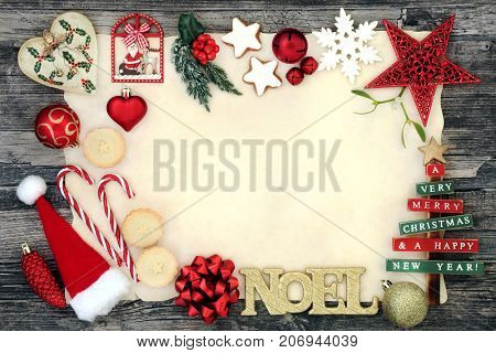 Christmas background border with noel sign, bauble decorations, mince pies, gingerbread cookies holly and fir on parchment paper on rustic wood.