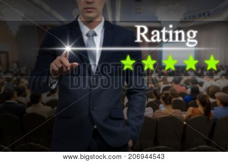 Businessman pointing five star button to increase rating of hotel over Abstract blurred photo of conference hall or seminar room with attendee background business evaluation concept Increase rating