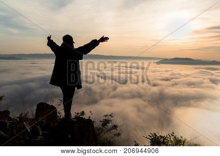 silhouette of woman who show hands over the mountain with fog landscape on morning at phu pha duk Nong Khai Thailand.