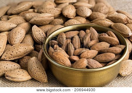 Almonds peeled in a bowl or in their nutshell