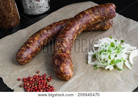 Two raw sausages with onion and spices