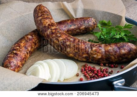 Two raw sausages in a frying pan with onion spices and parsley