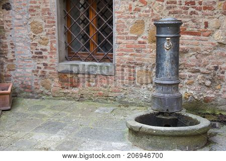 Ancient fountain to quench your thirst in a country lane in Italy